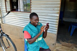 Community health worker using his mobile phone with upSCALE app