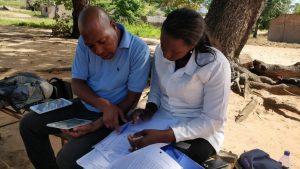Mozambiquen upSCALE Malaria Consortium technician and CHW cross checking data books with upSCALE app