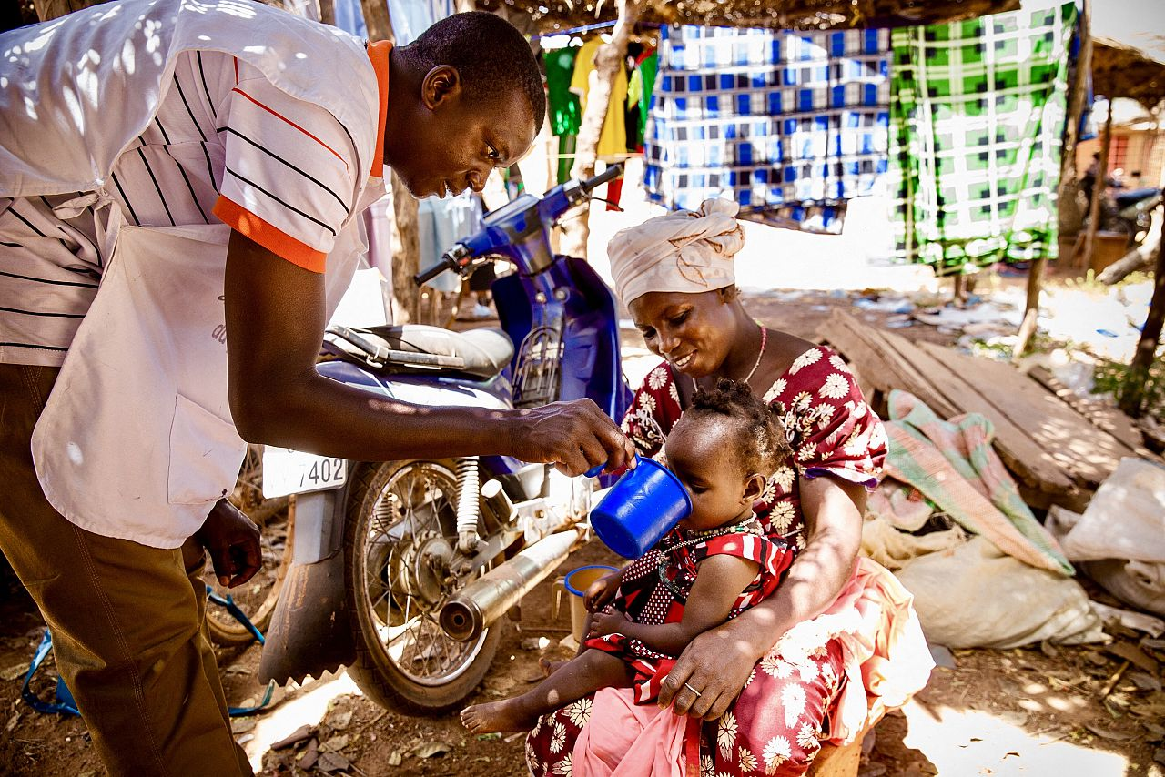 Community distributor dispensing SMC to a child in Burkina Faso