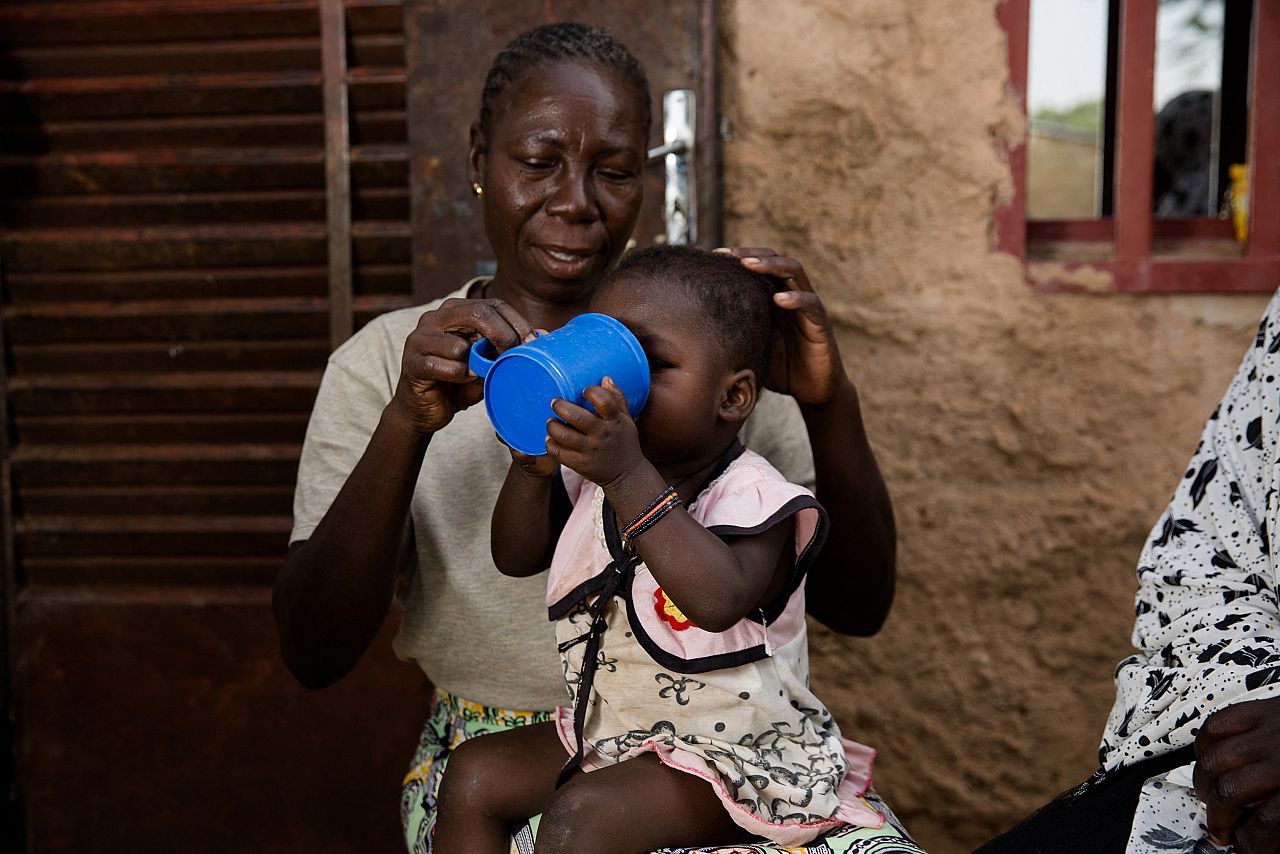 A mother helps her child to take SMC medication in Burkina Faso (Credit: Sophie Garcia/Malaria Consortium)