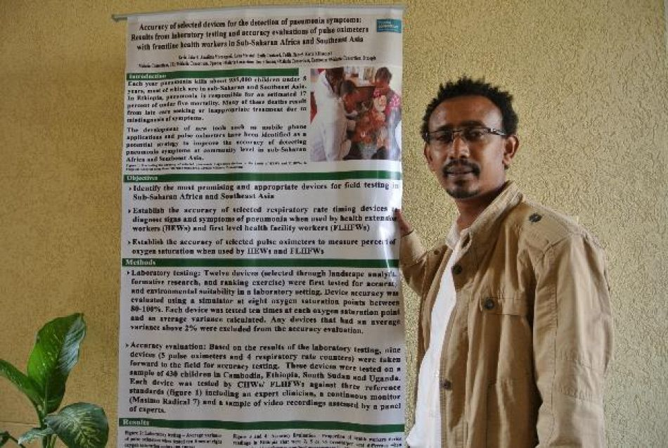 pTedila Habte Project Manager Pneumonia Diagnostics with a poster demonstrating laboratory test and accuracy results of selected devices for detection of pneumoniap