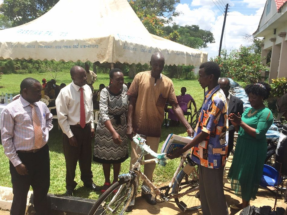 pA member of the village health team receives the first bicycle which is officially presented to him by district leadersp