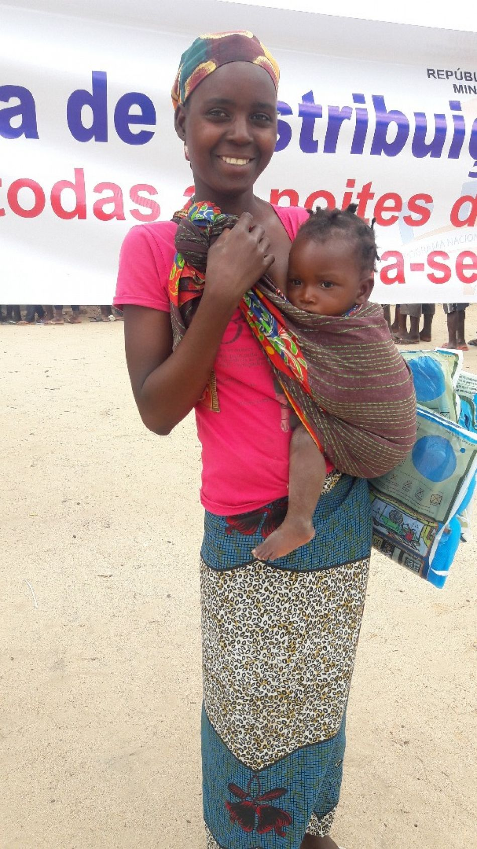 pYoung woman and her child are happy to receive nets in Cidade Nampulap