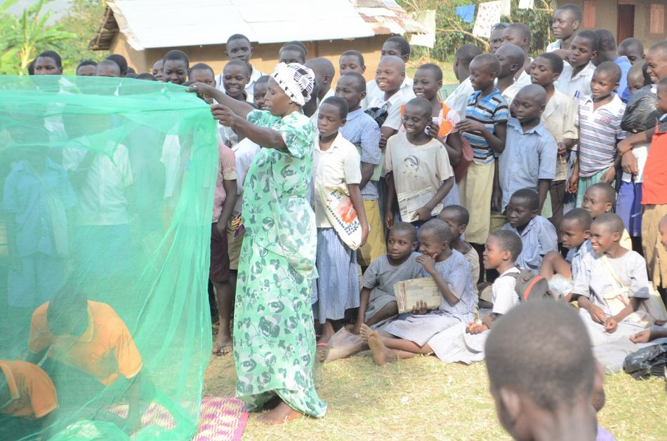 pCommunity members and in particular the young children watch as the performers teach them how to hang a mosquito net before going to sleepp