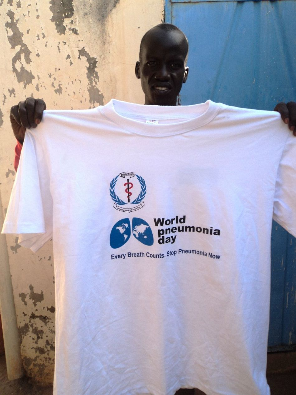 pPneumonia Diagnostics Research Assistant Gabriel Garang holding up thenbspa tshirt for World Pneumonia Dayp