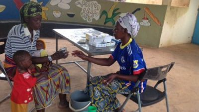 Community Health Worker gives a mother the SMC mixture to give to her baby