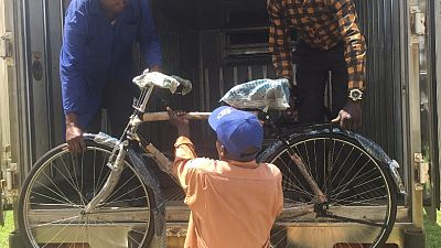 The last bicycle is unloaded in Iyolwa as the members of villages health teams begin to arrive to collect their new bicycle.