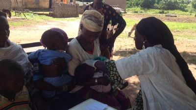 A Community Health Worker helps a mother to administer the SMC medication