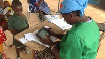 A Community Health Worker fills in the beneficiary's details