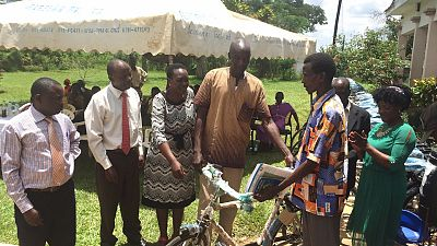 A member of the village health team receives the first bicycle, which is officially presented to him by district leaders.