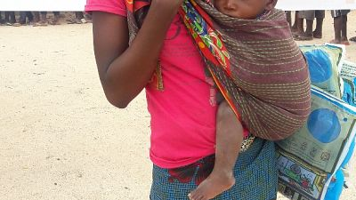 Young woman and her child are happy to receive nets in Cidade, Nampula