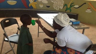 A Community Health Worker administers SMC to a child under five years old