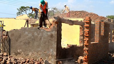 Workers on site knock down the walls of the old health centre.