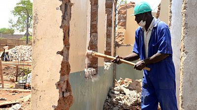 Moses Owori, Foreman, helps to knock down the walls of the clinic.