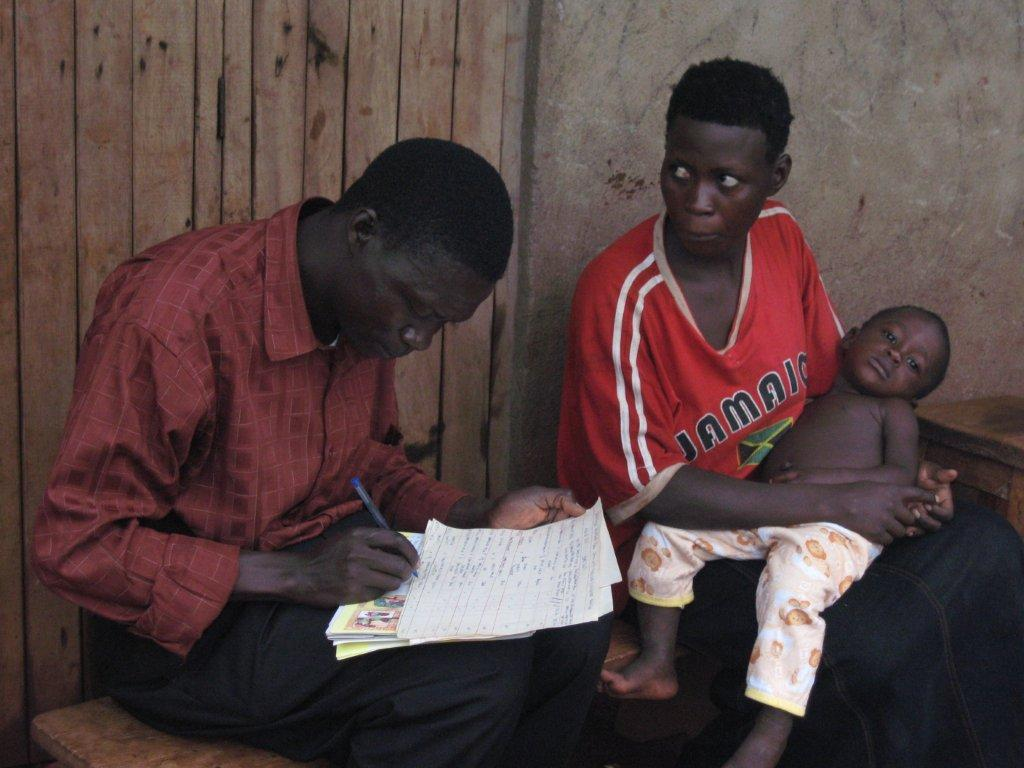 Community health worker recording treatment for a sick child